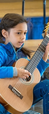 Female Daycroft student playing guitar.